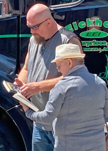 Independent owner-operator trucker Jeremy Johnson picks up Teamster Rebellion, Teamster Politics and Militant subscription from Jacquie Henderson, right.