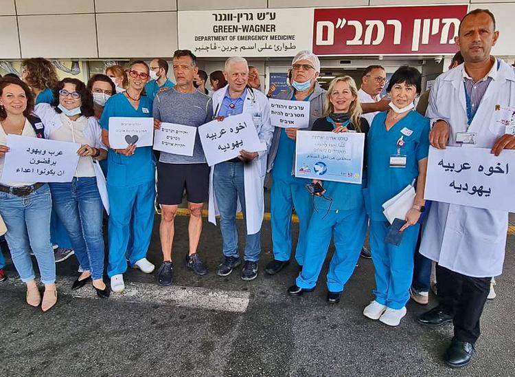 """Trabajadores árabes y judíos en centro de salud Rambam en Haifa, 16 de mayo. Letreros en árabe y hebreo leen """"judíos y árabes rehusan ser enemigos"""". Esto es clave para lucha de clases."""