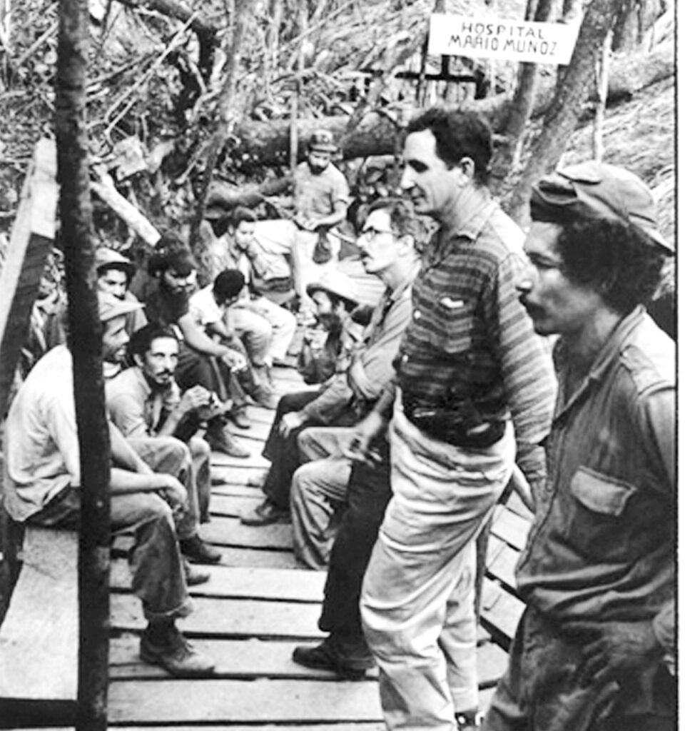 Working people and Rebel Army fighters line up at field hospital in Sierra Maestra, Cuba, 1958. Revolutionary forces' policy was to treat peasants, combatants, wounded enemy soldiers without distinction.