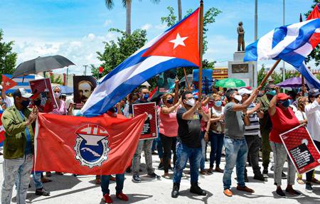 Trabajadores con bandera de la Central de Trabajadores Cubanos, izq. en protesta en Bayamo, Cuba, el 12 de julio. El pueblo trabajador se manifestó para defender la Revolución Cubana de la injerencia de Washington y sus esfuerzos para aumentar la presión internacional contra Cuba. Washington se rehusa a poner fin a su guerra económica contra Cuba.