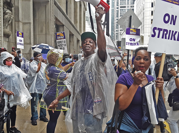 Over 400 hospital workers on strike in Chicago area rally June 29 outside Cook County president's office in fight for more pay and against high cost of health care coverage.