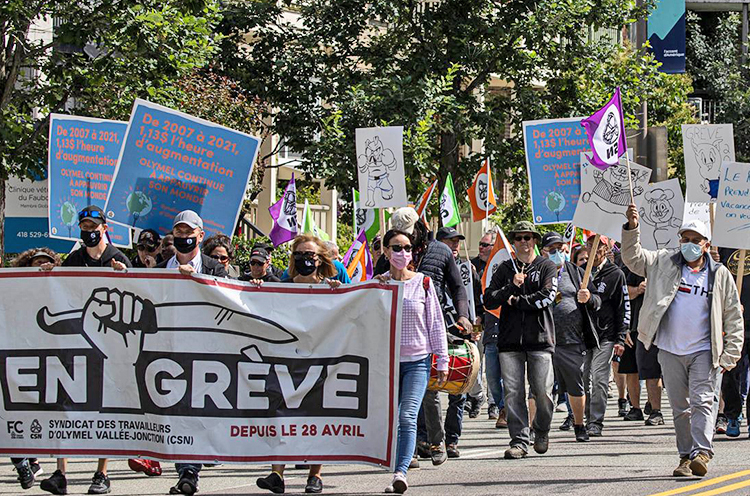 """Olymel meatpackers carry """"on strike"""" banner in Quebec City march July 7 demanding bosses negotiate a new contract. Bosses seek to keep steep wage cuts imposed on workers in 2007."""