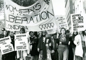 """Maya Forstater, inset, won victory June 10 at London's Employment Appeal Tribunal after being dismissed from job for stating that biological sex is """"real, important, immutable."""" This is a precondition for battle to win women's emancipation. Above, major women's rights march in 1979 in London."""