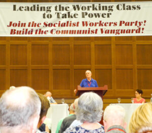 Jack Barnes, SWP national secretary, speaks at conference. SWP leader Mary-Alice Waters, right. Banner captured central themes of conference presentations, classes, discussions.
