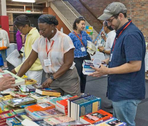 Des participants à la conférence feuillettent des livres qui s'ajouteront à leur bibliothèque marxiste.