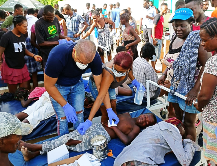 Volunteer Cuban health workers treat earthquake victims, other patients outside hospital in Corail, Haiti, Aug. 24. Cuban internationalists have worked continuously in Haiti for 22 years.
