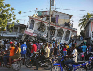People gather outside Petit Pas Hotel, destroyed by Aug. 14 earthquake in Les Cayes, Haiti. Impoverished by U.S. imperialist plunder, thousands were killed, injured or made homeless.