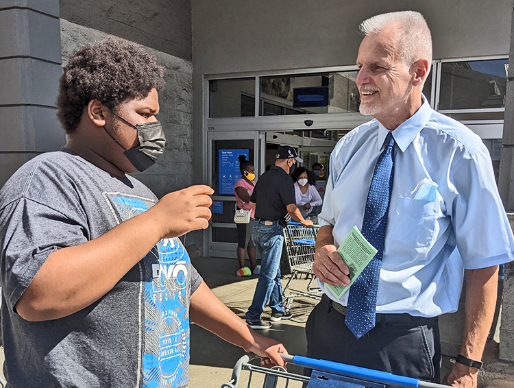 """Dennis Richter, right, SWP candidate for governor of California, talks with high school student Marcus Connelly at L.A. Walmart Aug. 5. Connelly said U.S. government should have made sure everyone could get vaccinated and jabs were given """"to poor countries around the world."""""""