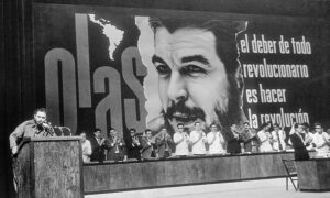 """Delegates from revolutionary organizations in the Americas clap as Cuban President Fidel Castro addresses August 1967 conference of Organization of Latin American Solidarity in Havana. The slogan beside the image of Che is from the Second Declaration of Havana. It reads, """"The duty of every revolutionary is to make the revolution."""""""
