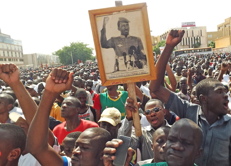 """""""The democratic and popular revolution needs a convinced people, not a conquered people,"""" says the sign above, quoting revolutionary leader Thomas Sankara under his photo. It's carried in a June 29, 2013, protest against Blaise Compaore, who led the 1987 counterrevolution."""
