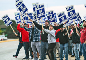 """Picket at John Deere Davenport, Iowa, factory first day of strike Oct. 14 by 10,000 members of United Auto Workers. """"We're not going to sell new hires down the river,"""" said strikers."""